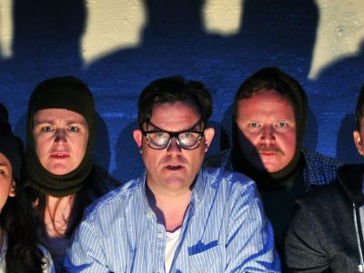 Five actors all looking shocked standing shoulder to shoulder against a wall of shadows