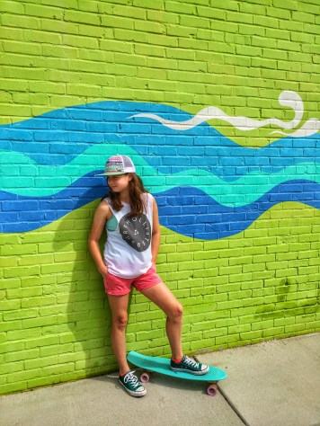 Amy Lyon Smith's daughter in front of an art wall in Carolina Beach, North Carolina with her Penny board
