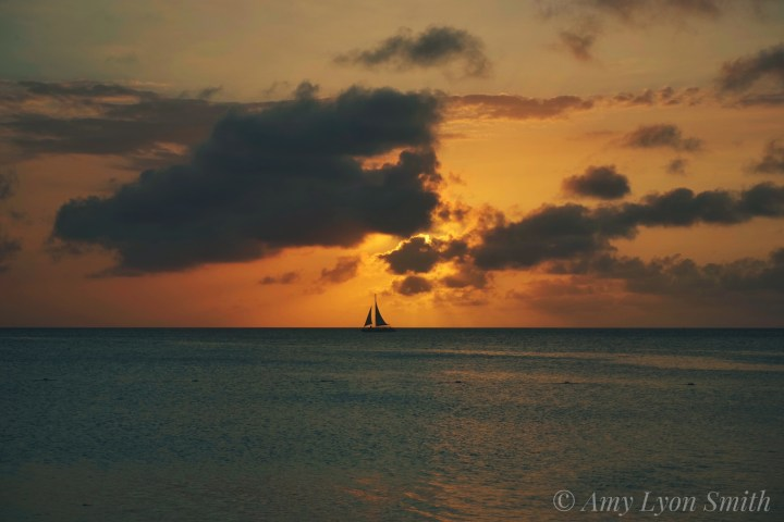 sunset photo in aruba with sailboat on the ocean