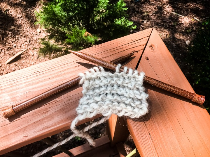 Learn to knit.  Knitting needles and yarn stitched in a garter stitch.