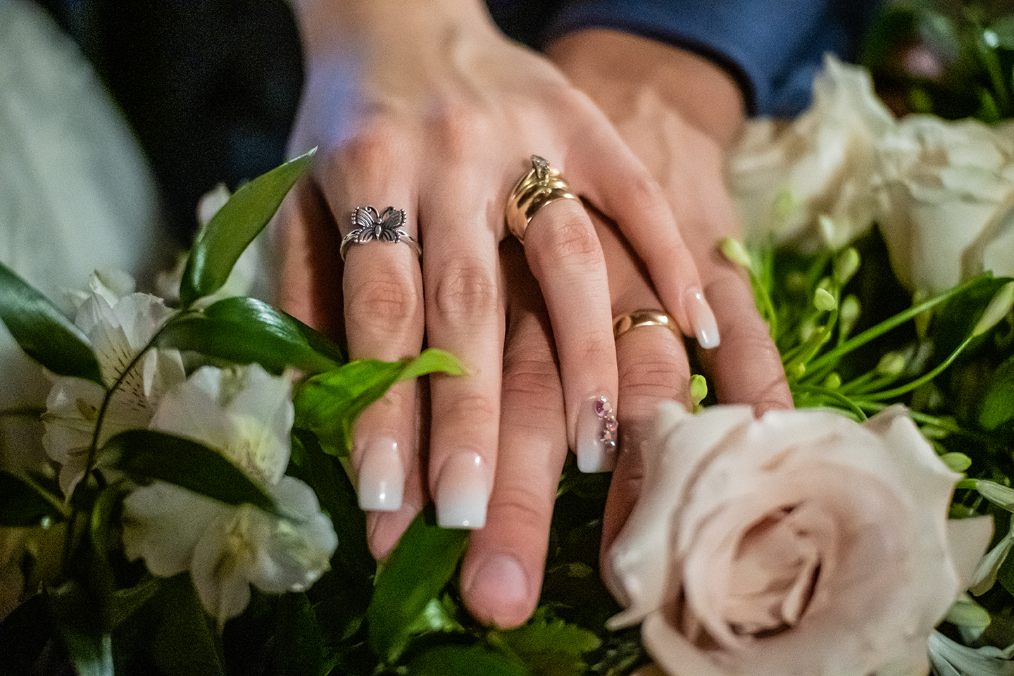With their hands resting on pink and white flowers the bride and grooms hands touch for a close up detailed shot of their wedding bands at The Grand Hacienda at Skipper Ranch located in Encino, Texas.
