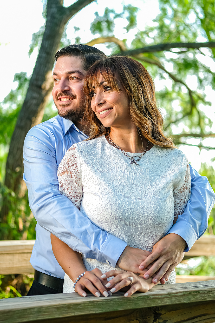 A man in a blue button down hugs his fiancé, in a elegant white dress from behind, as they stare off into the distance while standing on a dock on a lake in the Edinburg Municipal Park in Edinburg Texas.