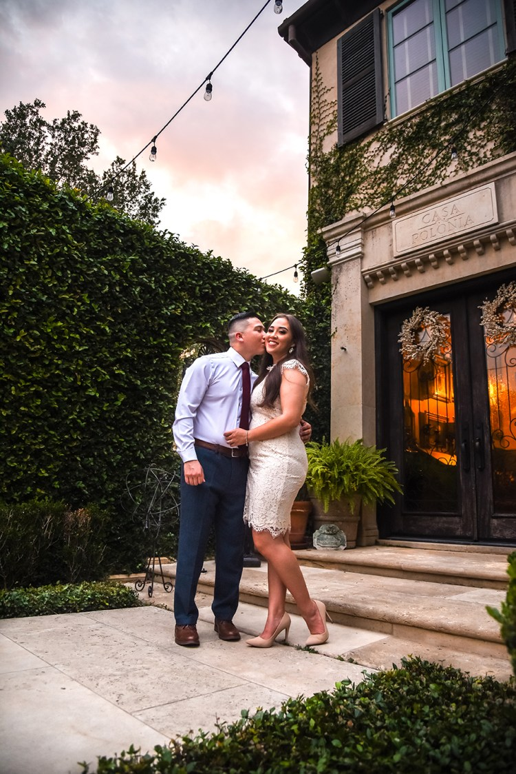 With one leg raised a woman holds onto her fiancé. He lovingly kisses her cheek. They stand before an amazing overcast sky with the reds of the setting sun, and before the beautiful architecture of the Casa Polonia in Weslaco Texas. There is a wall of lush green nature working its way up the building.