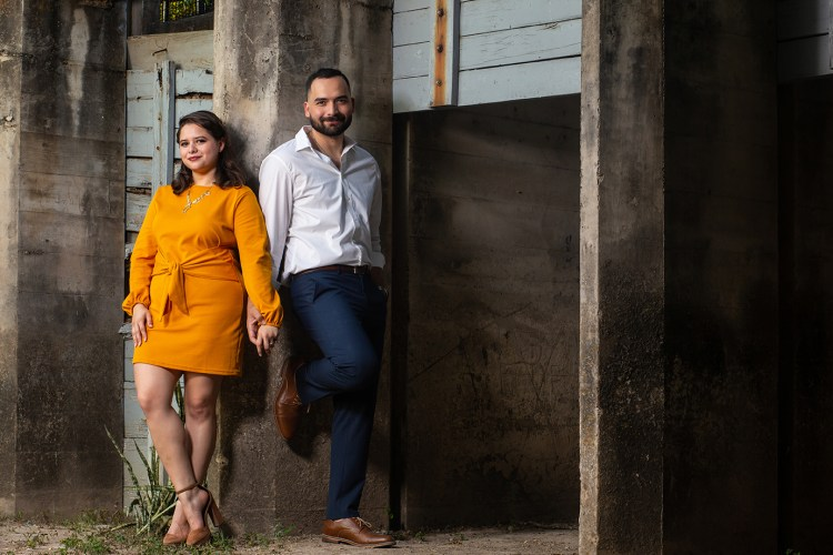 A young woman in an orange dress holds the hand of her fiancé standing next to her, in his white button down and navy blue kakis, as they lean against a textured wall at Old Hidalgo Pumphouse in Hidalgo Texas.