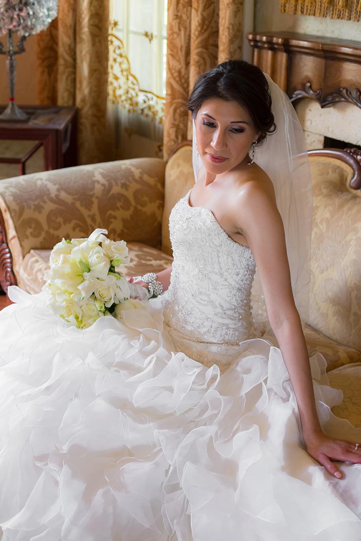 Bride sitting with bouquet posing for camera at Quinta Mazatlan in McAllen, Texas.