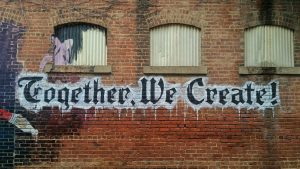 """Together We Create"" Painted on a Brick Wall"