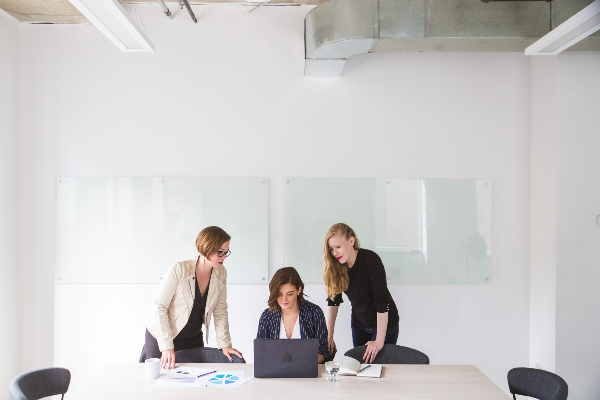 Three women in office looking at computer