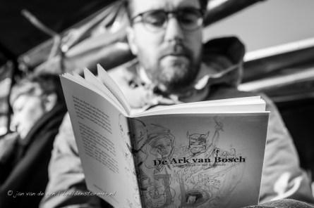 een deelnemer aan 'varen met jheronimus' leest met de declamerende dichters mee uit de bundel waarin de speciaal voor dit evenement geschreven gedichten zijn verzameld
