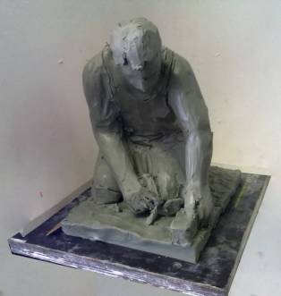 rough sketch in plasticine for a stone statue of a road worker