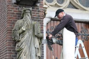 sculptor Koen van Velzen cutting the statue of Moses from Lambertus church in Veghel with a concrete chainsaw / diamond chainsaw