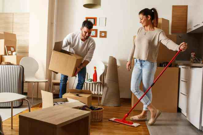 Young couple cleaning an a room full of moving boxes.