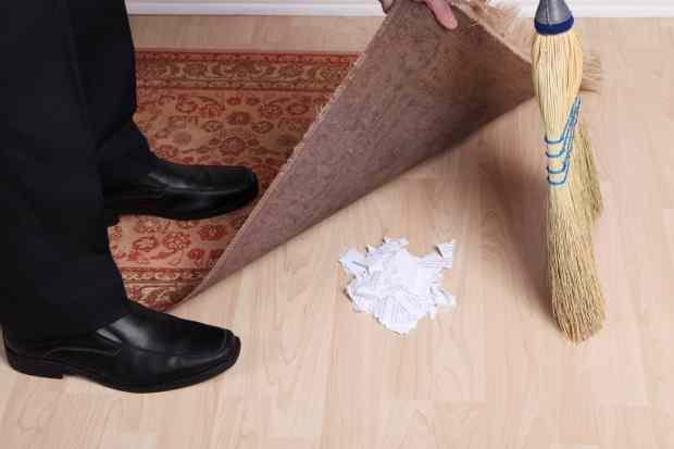 man sweeping dirt under a rug
