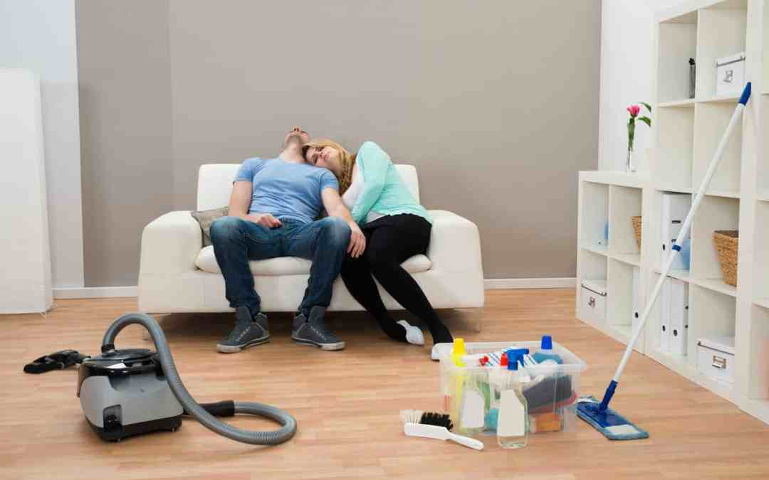Exhausted Couple Resting On Sofa In Living Room with cleaning supplies abandoned