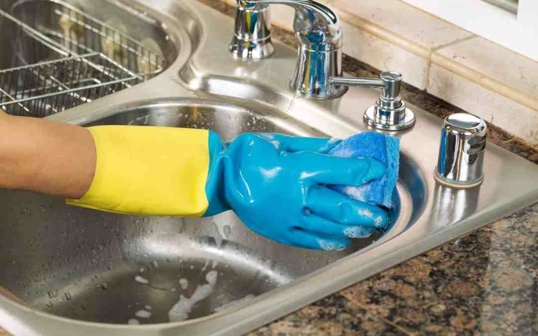 hand wearing rubber glove washing inside of kitchen sink with sponge and soapy water