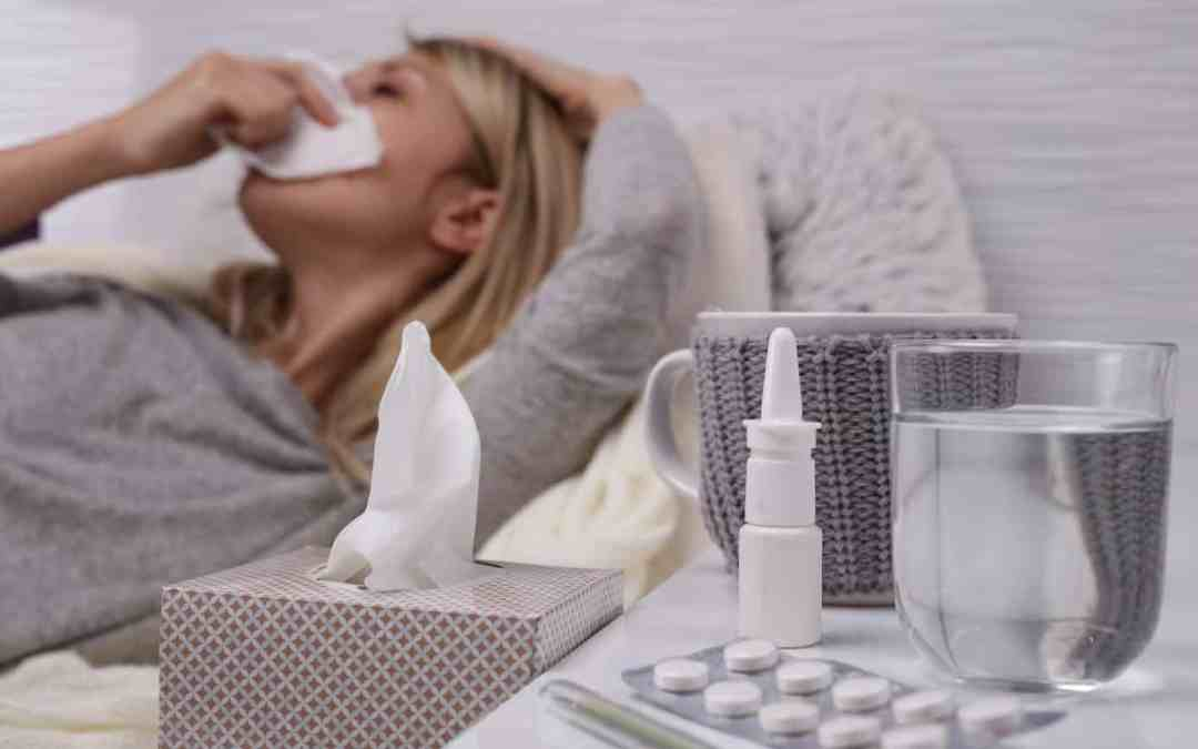 Woman sick in bed with cold or flu, running nose, selective focus on tissue box.