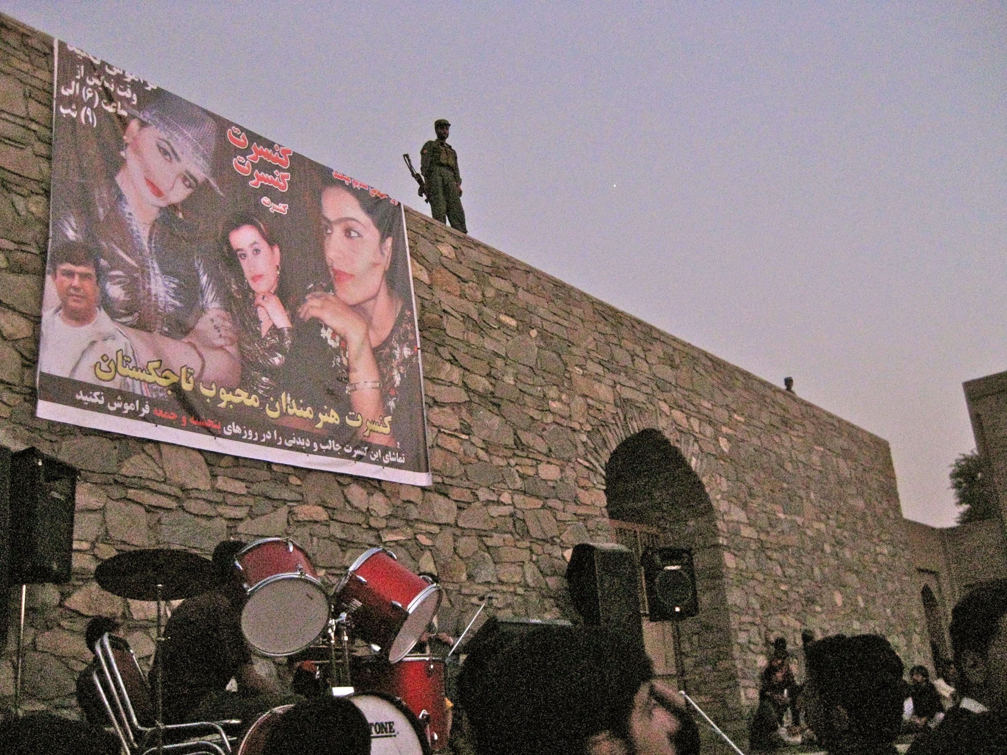 Tajik women concert banner with guard on wall