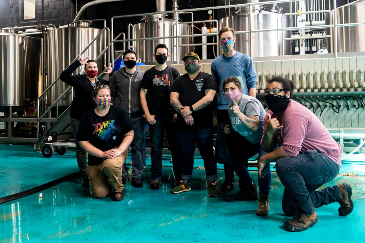 Tyler Mithuen (3rd from R) and Mai Jakubowski (2nd from R) pose with other members of Deviant Minds during a brew day at Modist Brewing Company • Photo via Deviant Minds