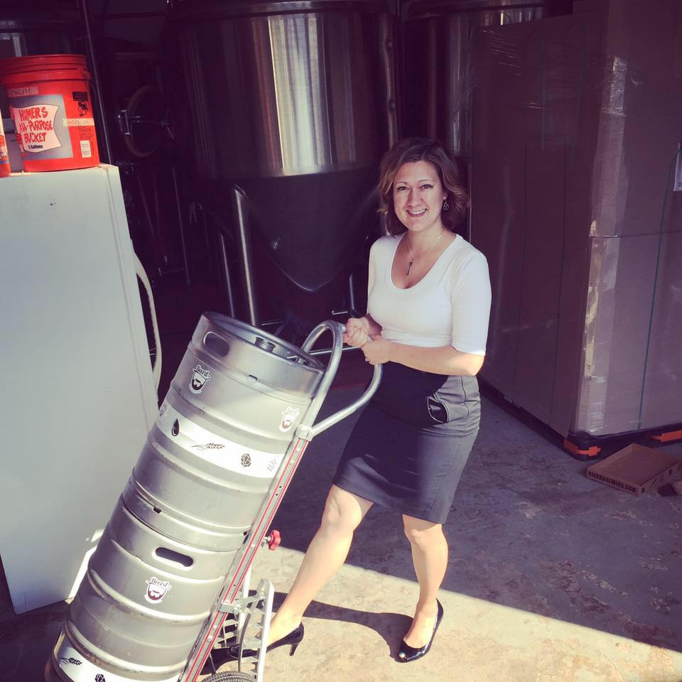 Precious Putnam, dressed up pushing a couple kegs on a dolly