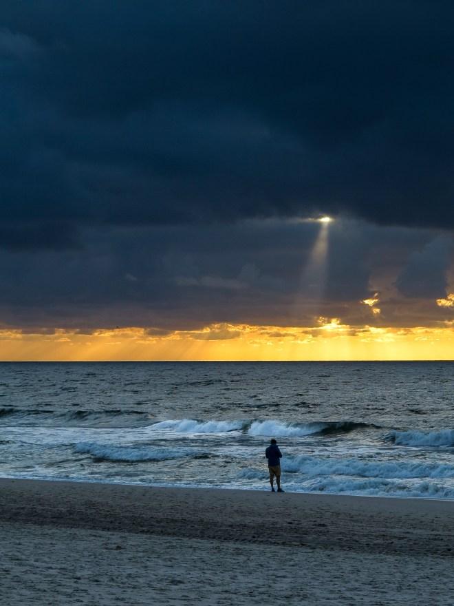 Sylt Strand Beach Mann Sonne bricht durch Wolken