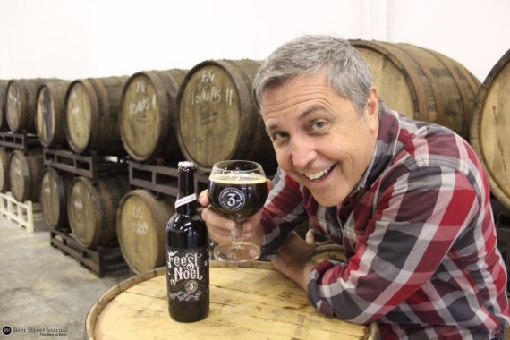 Three Taverns founder Brian Purcell shows off Bourbon Feest Noel in the brewery's barrel room.