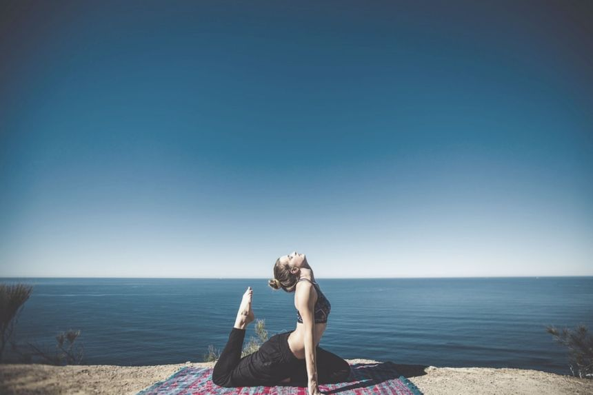 woman doing yoga by the sea natural pain relief through exercise