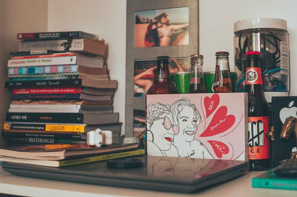 shelf with stacked books laptop and drink bottles