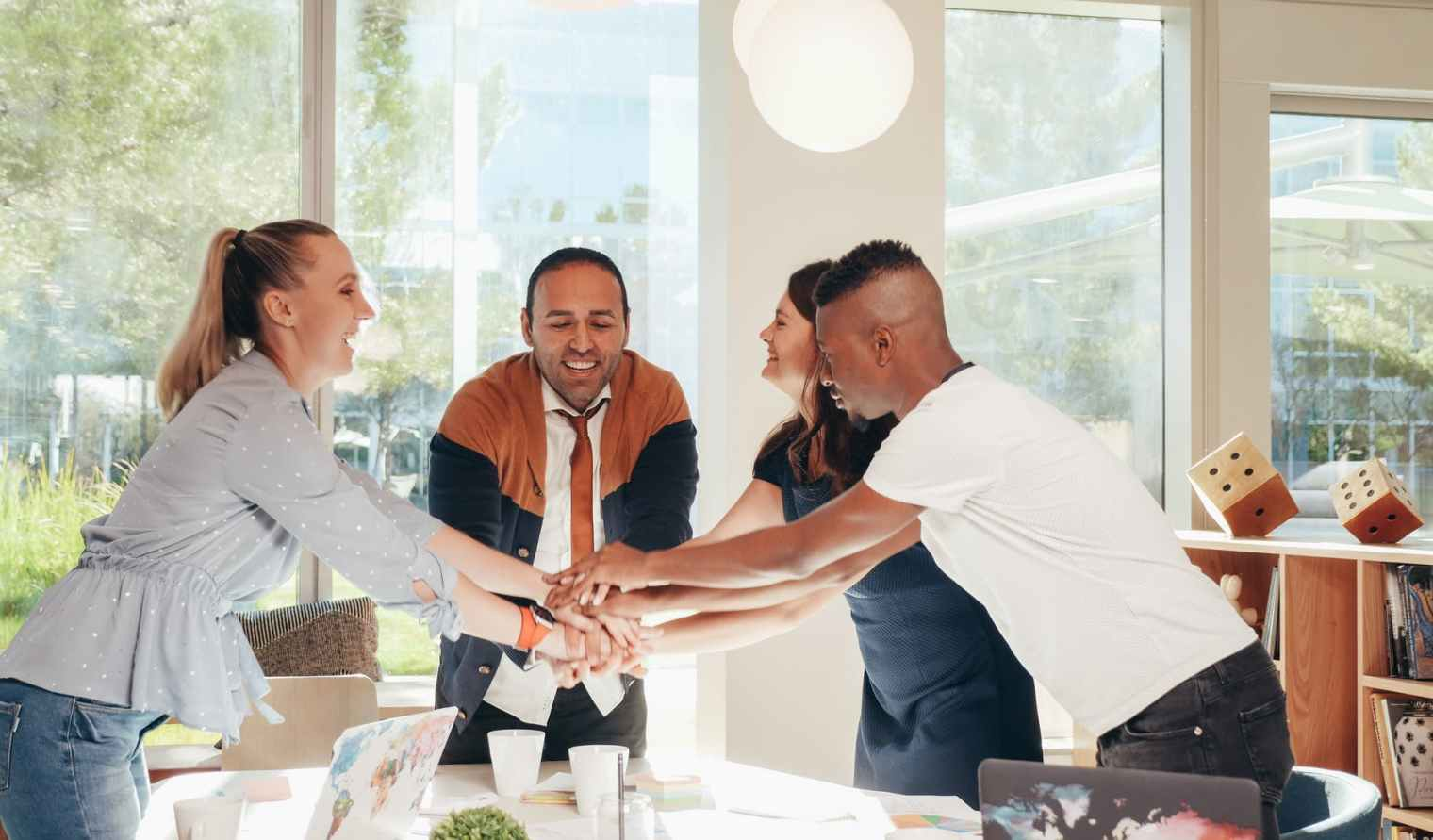 smiling multiracial coworkers with hands together in office