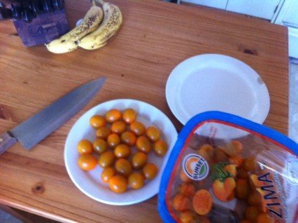 Get two plates, a sharp or serrated knife and the cherry tomatoes