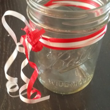 I wrapped two red and white ribbons around the jar, then tied them in a knot and curled the ends.