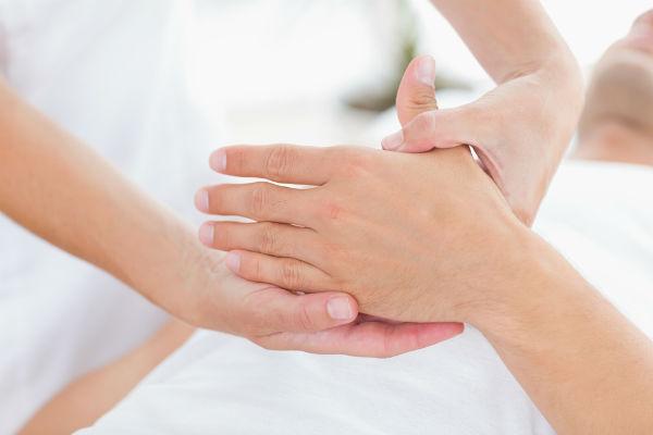 Behandler som presser på et område av hånden til en pasient