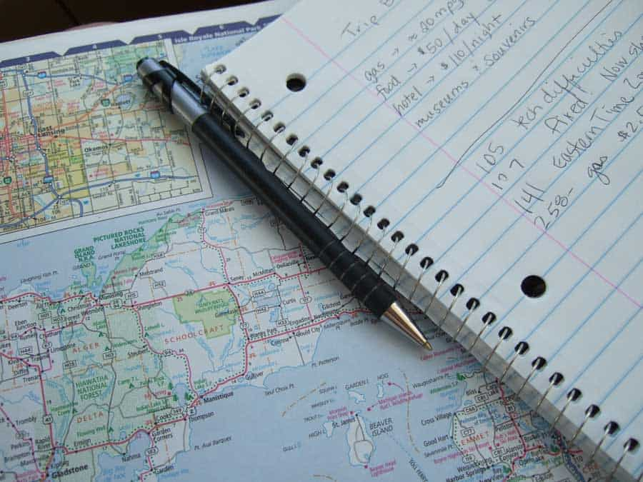 Using an atlas and my notebook to record my travels