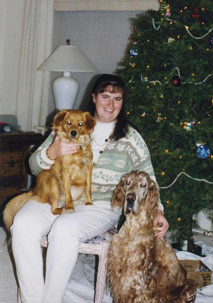 woman by christmas tree with two dogs