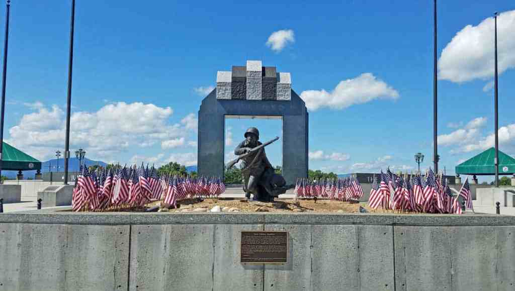 At the National D-Day Memorial, the Valor, Fidelity, Sacrifice sculpture is perfectly framed by the Overlord Arch. Along the sides you can see the flagpoles which are used to fly the 12 Allied countries' flags.