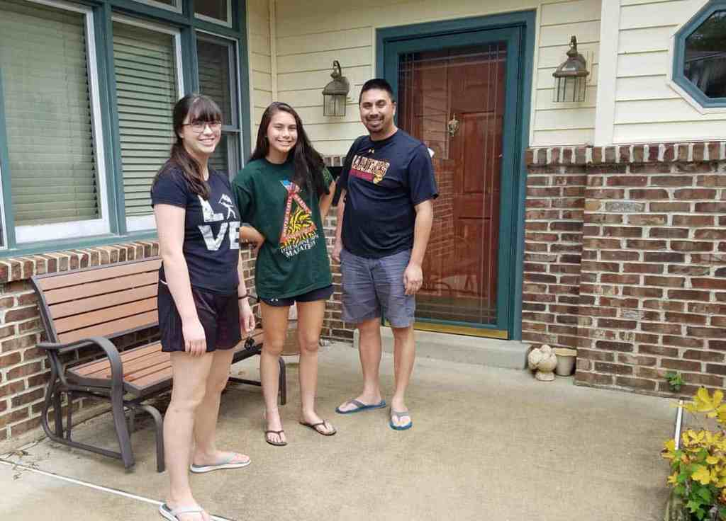 Man and two girls standing outside the front door of home
