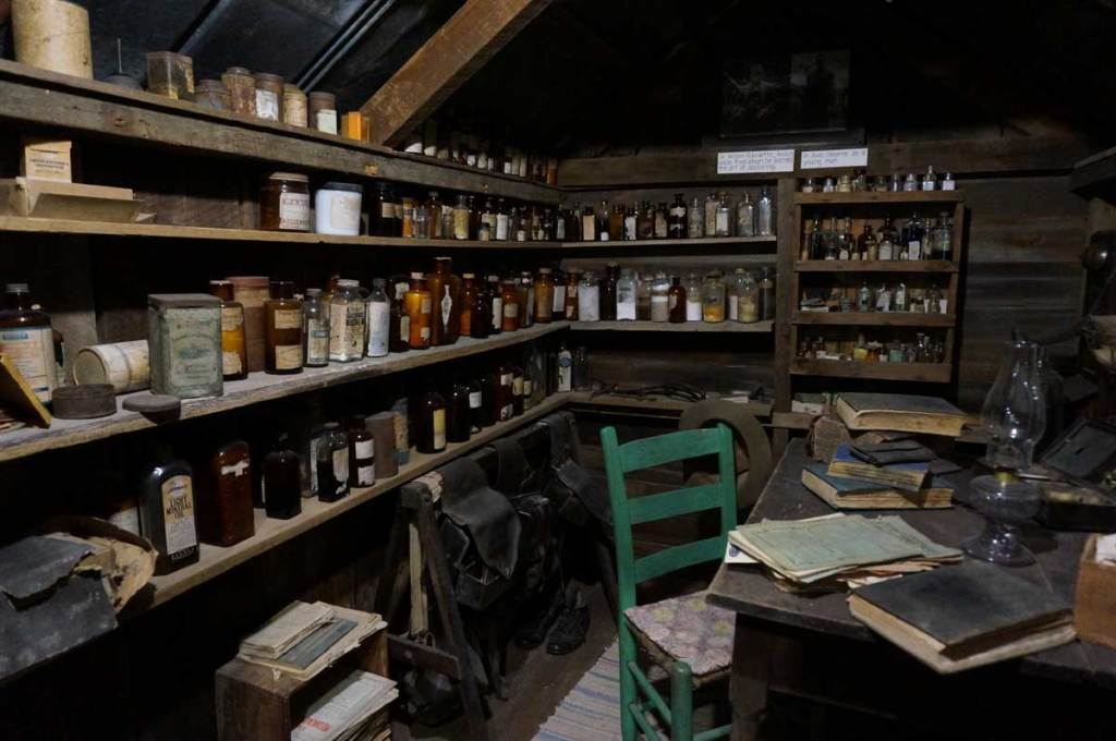 Looking inside the small shack that housed the local doctor's herbs and medicines with paperwork on the desk.