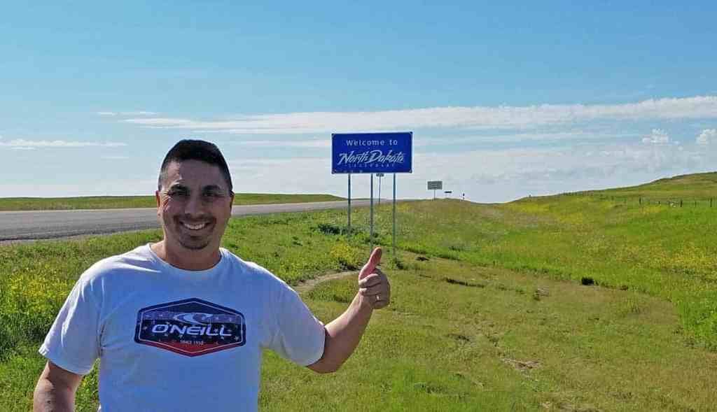 Man standing at side of the road in front of a Welcome to North Dakota sign displaying a thumbs up sign.