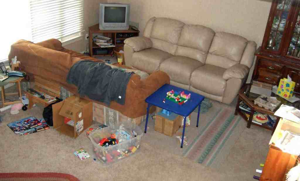 looking down on a living room with two couches and lots of toys everywhere