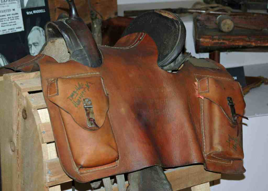 An original mochila displayed over a saddle in the Marysville, KS pony express museum