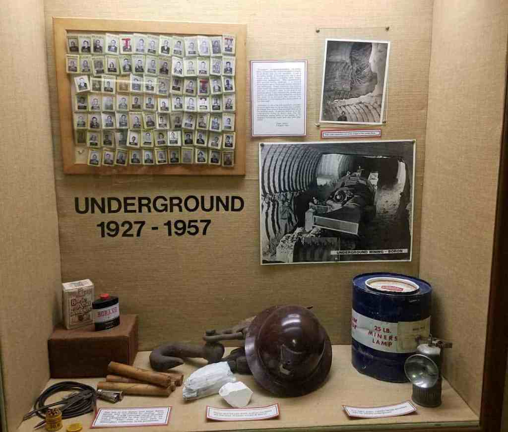 museum display of equipment used in underground mines and photos of miners id badges and equipment in the mine