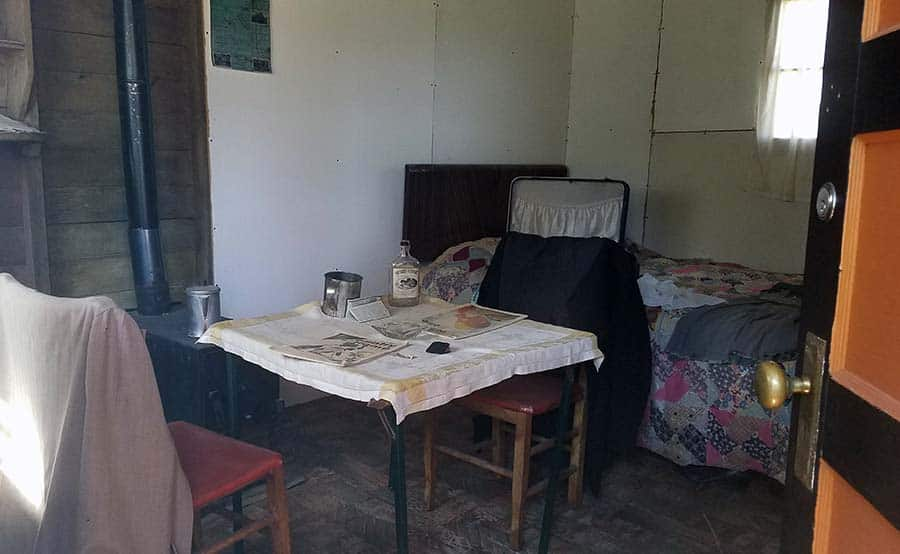interior of an early 1900s travel lodge cabin with a wood stove, card table, and bed.