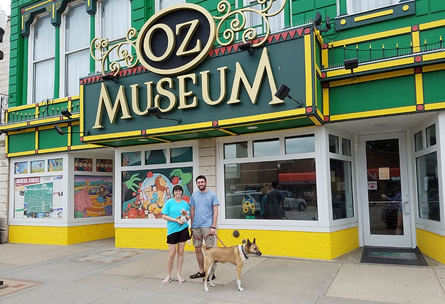 two people and dog stand outside the Kansas OZ Museum