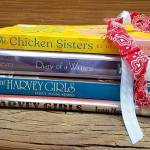 Stack of books with decorative ribbon (titles are Chicken Sisters, Diary of a Waitress, and The Harvey Girls)