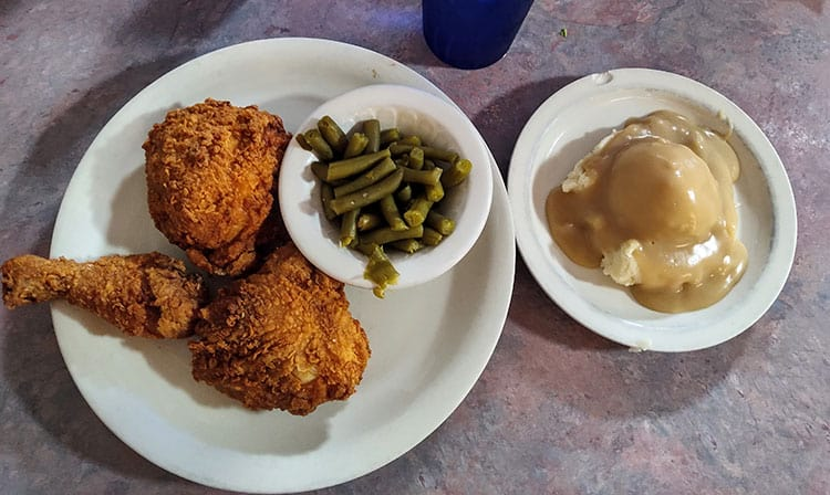 looking down at plate of fried chicken, green beans, and mashed potatoes with gravy