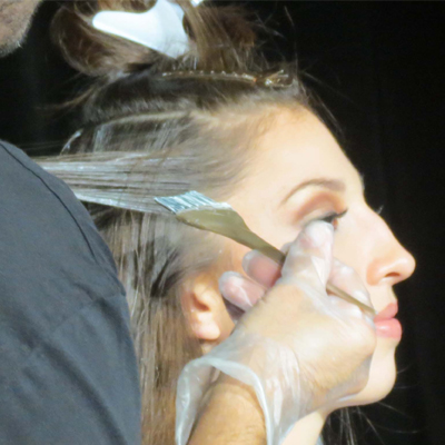 hand painting balayage highlights around the face
