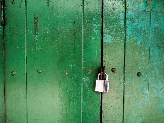 green wood door with silver padlock on it