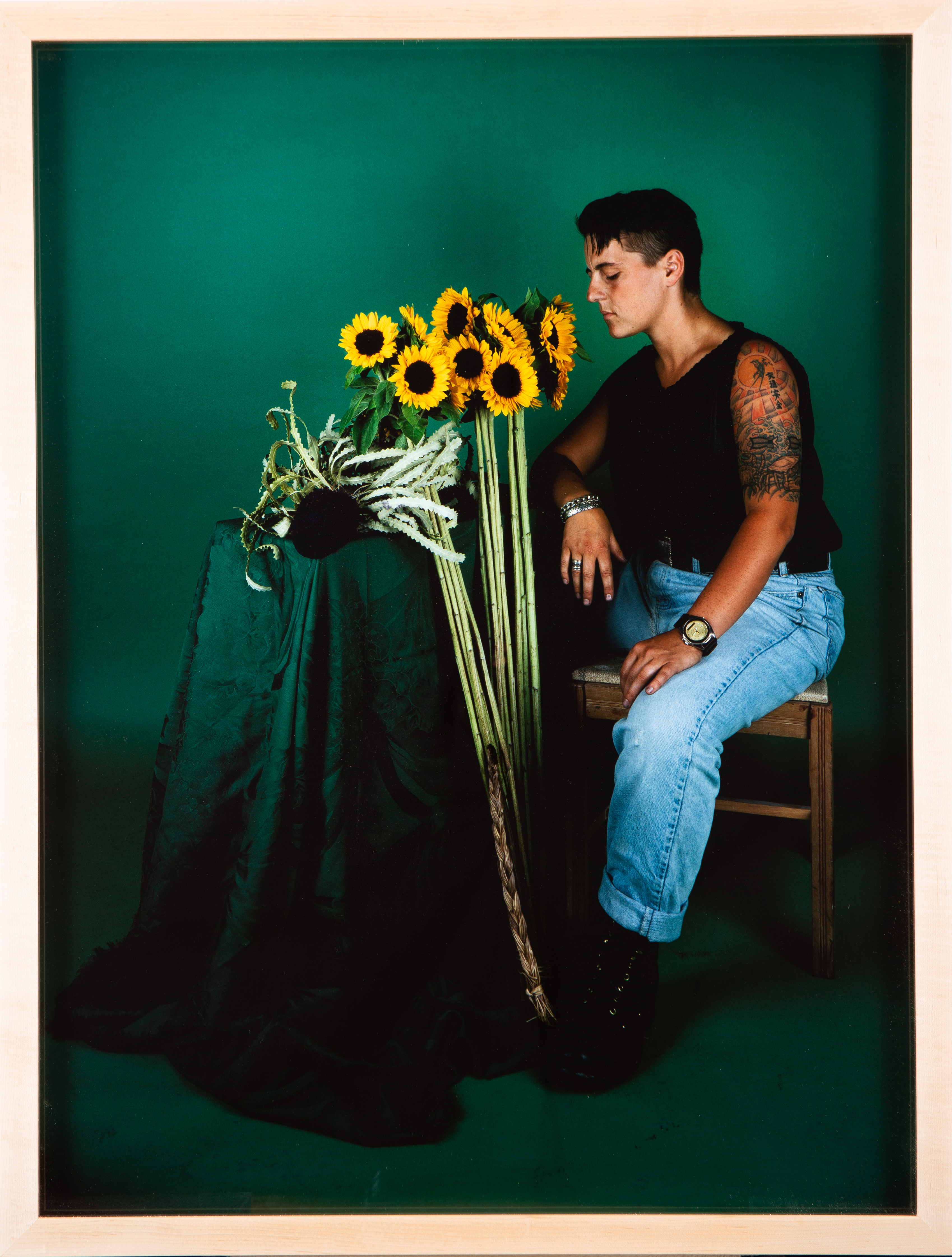 Seated, young, light-skinned adult with tattooed arm faces standing sunflowers in a green room