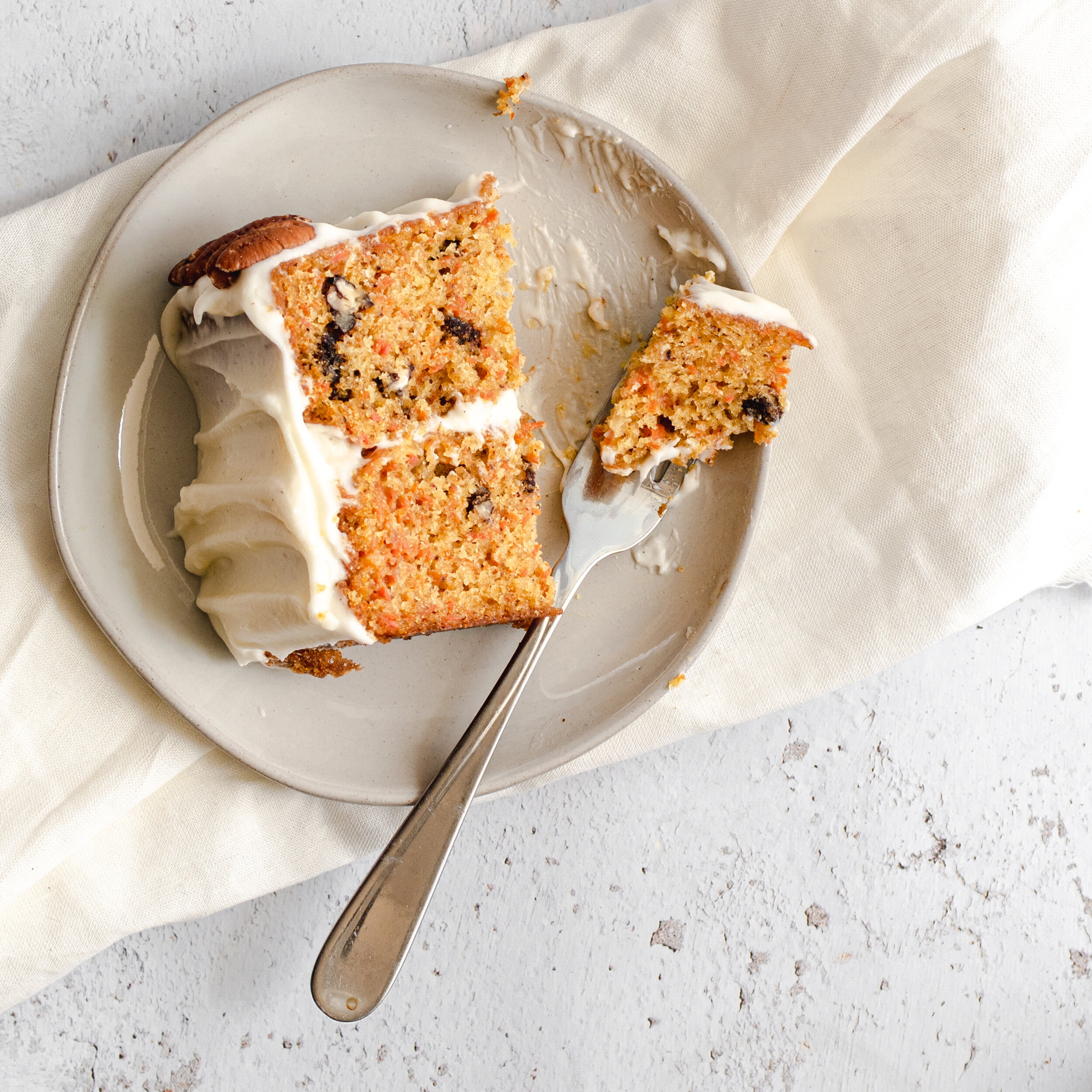 A slice of Southern mayonnaise carrot cake with a bite on a fork.