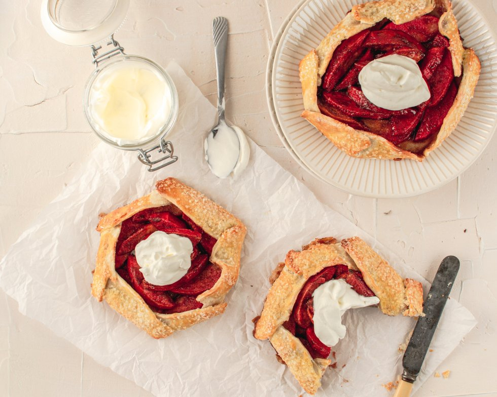 Overhead shot of three apple galettes with homemade whipped cream.