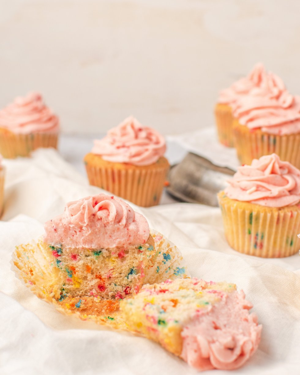 Champagne funfetti cupcake sliced open to reveal the inside soft crumb and colorful sprinkles