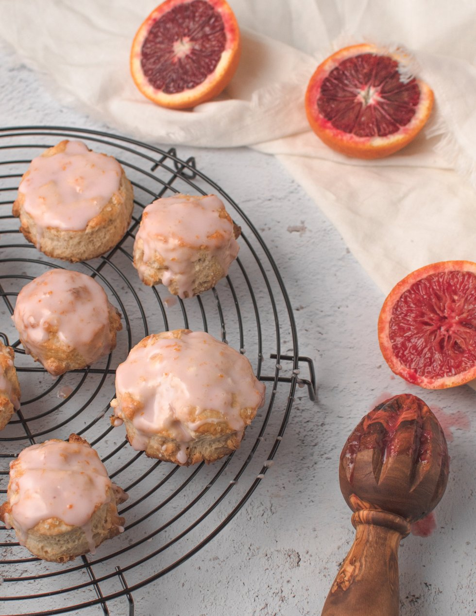 Blood orange scones with white chocolate chips and a blood orange glaze drip on a cooling rack next to sliced blood oranges.